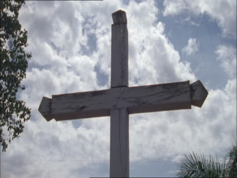 Clouds drift above a wooden cross.