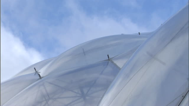 clouds drift above the honeycombed domes of the eden project. - イングランド南西部点の映像素材/bロール