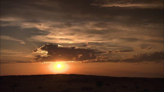 vídeos de stock, filmes e b-roll de clouds drift above the kalahari desert at sunset. - deserto de kalahari