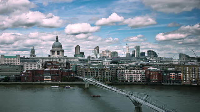 clouds drift above the millennium bridge and st. paul's cathedral in london. - london millennium footbridge stock videos & royalty-free footage