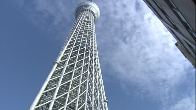 clouds drift above the tokyo skytree tower. - aufnahme von unten stock-videos und b-roll-filmmaterial