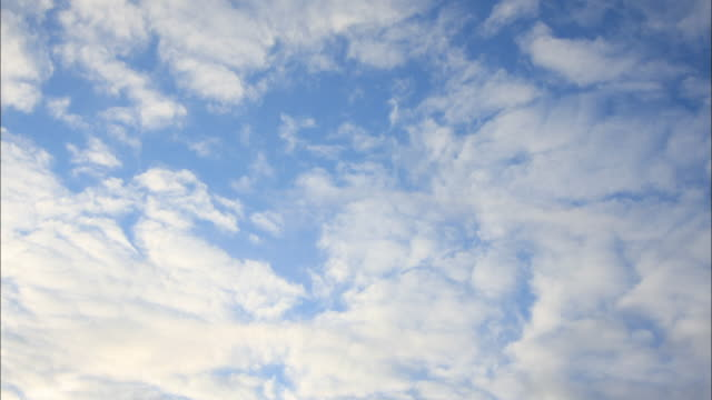 clouds drift across a blue sky. - sky only stock videos & royalty-free footage