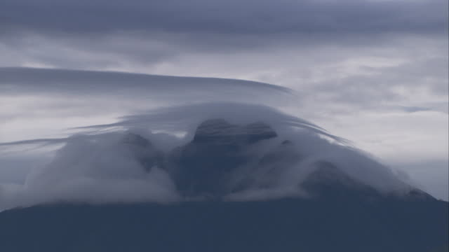 clouds drift across the summit of a volcano in the virunga mountains. available in hd. - parc national des volcans rwanda stock videos and b-roll footage