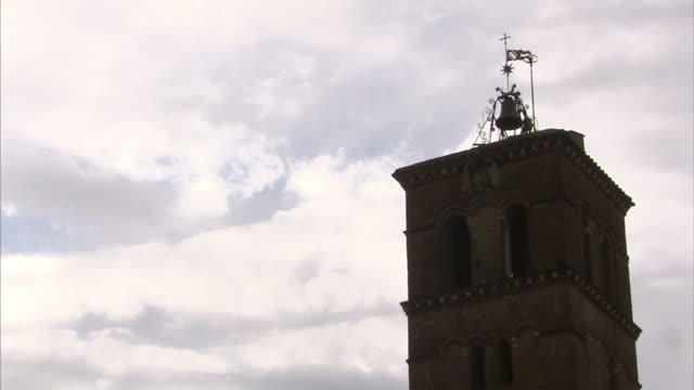Clouds drift behind the bell tower of the Church of Santa Maria in Trastevere in Rome, Italy.