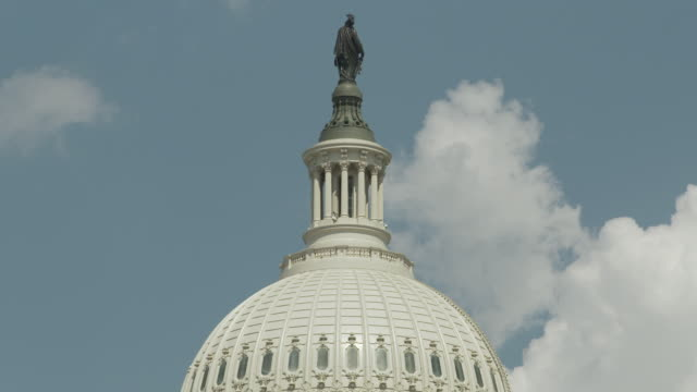 clouds drift behind the dome and statue of freedom on the united states capitol building on a sunny day, washington, d.c., usa. - demokratie stock-videos und b-roll-filmmaterial