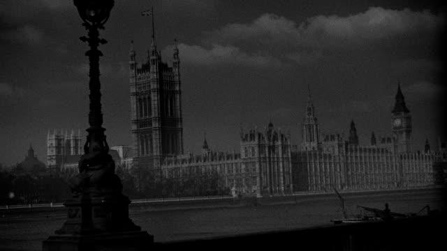 clouds drift behind the houses of parliament across the river thames in london, england. - victoria tower stock videos & royalty-free footage