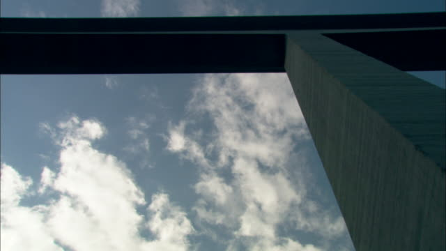 clouds drift over a high bridge. - colonna architettonica video stock e b–roll