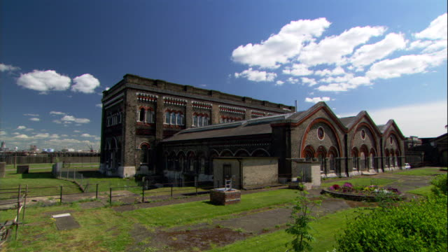 clouds drift over a london pumping station. - ポンプ場点の映像素材/bロール