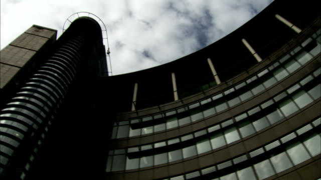 Clouds drift over a semi-circular building. Available in HD.