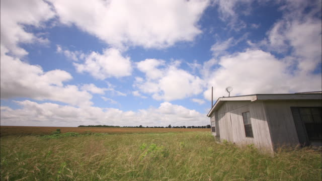 clouds drift over a solitary house in the countryside. - prärie stock-videos und b-roll-filmmaterial