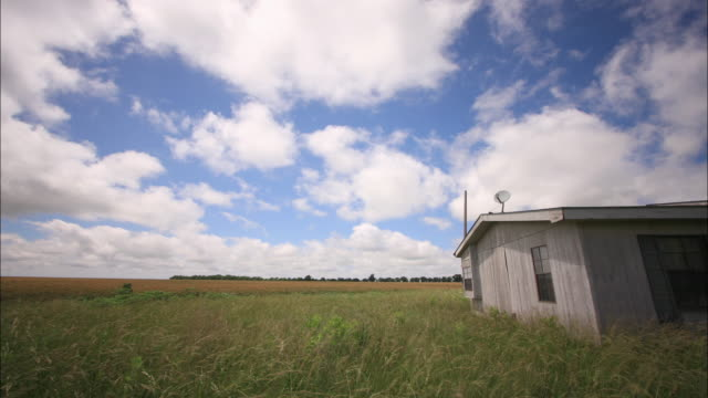 clouds drift over a solitary house in the countryside. - prairie stock videos & royalty-free footage