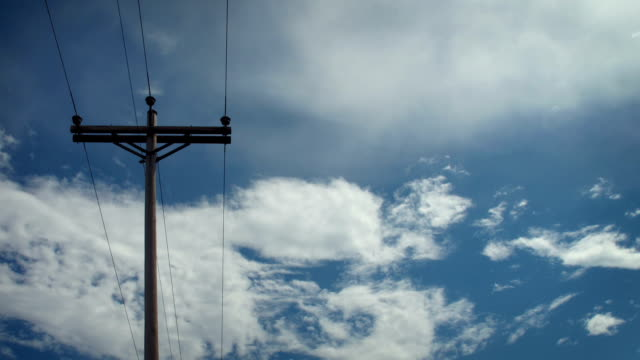 Clouds drift over a telephone pole.