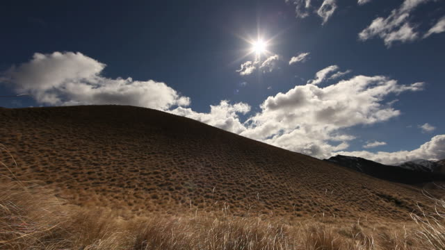 clouds drift over a tussock. - otago region stock videos & royalty-free footage