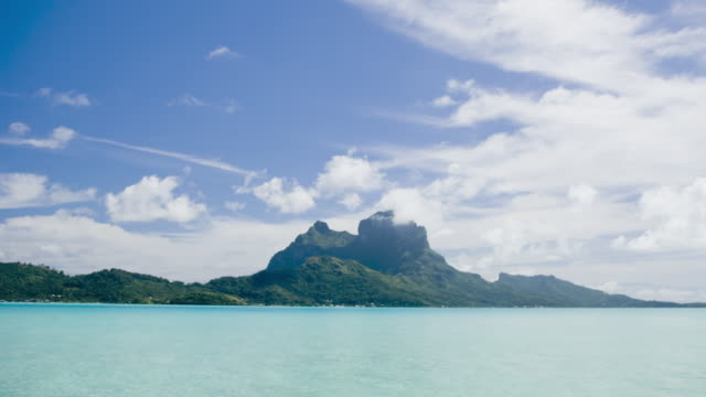 vídeos de stock, filmes e b-roll de clouds drift over bora bora. - polinésia francesa