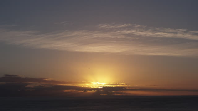 clouds drift over sea as sun rises. - sunrise dawn stock-videos und b-roll-filmmaterial
