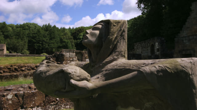 tl clouds drift over statue in mount grace priory, uk - female likeness stock videos & royalty-free footage