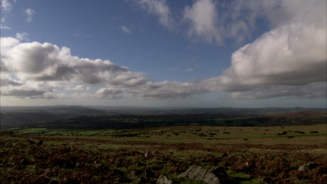 clouds drift over the british countryside. available in hd. - moor stock videos & royalty-free footage
