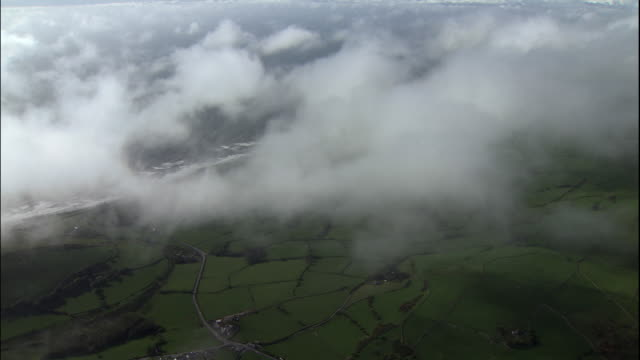 Clouds drift over the green farmlands of coastal Wales.