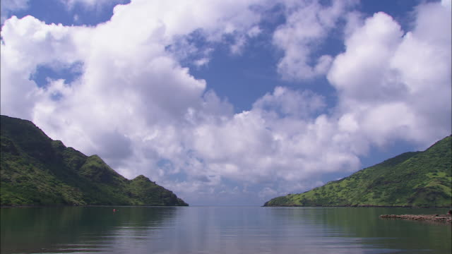clouds drift over the green mountains of komodo island. - insel komodo stock-videos und b-roll-filmmaterial