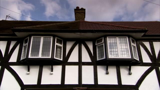 vídeos de stock, filmes e b-roll de clouds drift over the roof of a mock-tudor house, london. available in hd. - janela saliente
