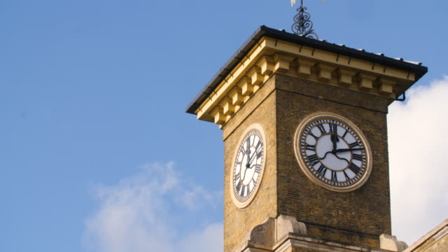 clouds drift past the clock tower on top of kings cross station, london. - clock face stock videos & royalty-free footage