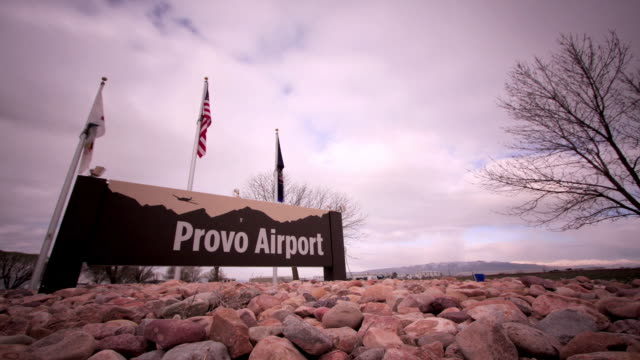 stockvideo's en b-roll-footage met clouds drift quickly over the entrance to utah's provo airport. - provo