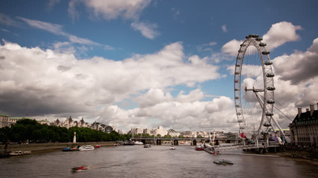 clouds drift through the sky over the london eye on the bank of the river thames. - ミレニアムホイール点の映像素材/bロール