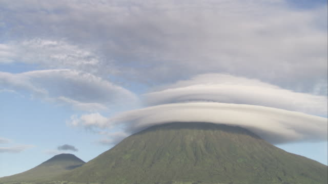 clouds encircle the peak of a volcano. available in hd. - parc national des volcans rwanda stock videos and b-roll footage