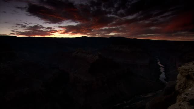 clouds fill a dramatic sky above the grand canyon at sunset. - grand canyon stock videos & royalty-free footage