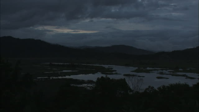 clouds fill the sky above a quiet marsh at night. - marsh stock videos & royalty-free footage