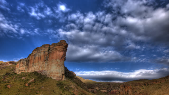 clouds float above sandstone cliffs. - drakensberg mountain range stock videos & royalty-free footage