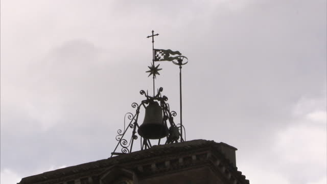 Clouds float behind a bell on the Church of Santa Maria in Trastevere in Rome.