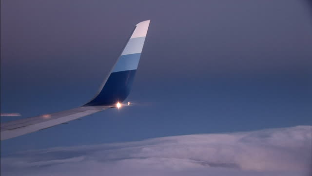 clouds float below the tail of an airplane. - airplane tail stock videos and b-roll footage