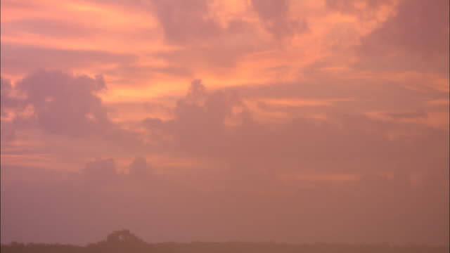 clouds float in a pink and purple sky. - pink color stock videos & royalty-free footage