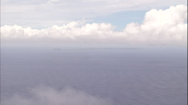 clouds float over iwo jima island on the horizon of the pacific ocean. - iwo jima island stock videos & royalty-free footage