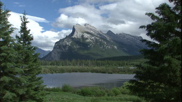 clouds float over mount rundle and a lake at banff national park. - montagne rocciose video stock e b–roll