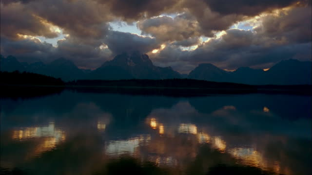 clouds float over silhouetted mt. moran and jackson lake in grand teton national park, wyoming. - mt moran stock videos & royalty-free footage
