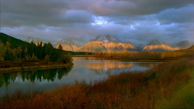 clouds float over snowy mt. moran and the snake river in grand teton national park, wyoming - mt moran stock videos & royalty-free footage