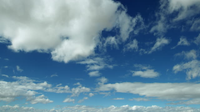 clouds float peacefully through blue sky - panorama di nuvole video stock e b–roll