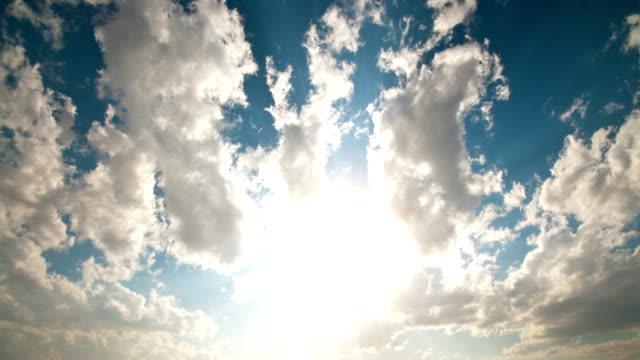 Clouds float through a sunny sky.