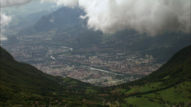 aerial ws clouds floating above cityscape and isere river with alps in background / grenoble, france - grenoble stock-videos und b-roll-filmmaterial