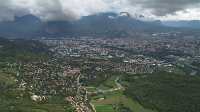 aerial ws clouds floating above cityscape with alps in background / grenoble, france - grenoble stock-videos und b-roll-filmmaterial