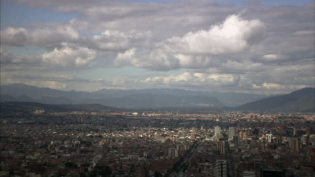 AERIAL WS Clouds floating above cityscape with hills in background / Bogota, Colombia
