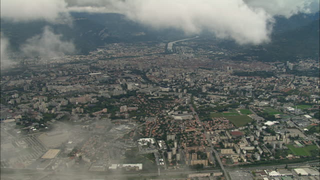 aerial ws clouds floating above cityscape with isere river and alps in background / grenoble, france - grenoble stock-videos und b-roll-filmmaterial