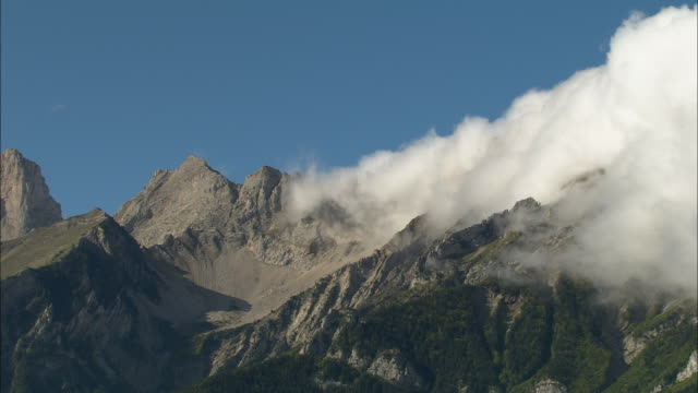 AERIAL WS Clouds floating above mountain peaks in Maritime Alpes / Rhone-Alpes, France