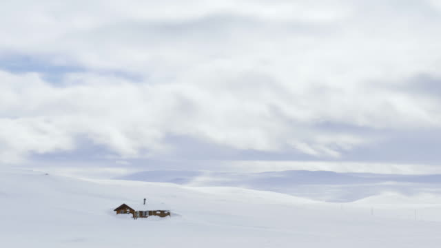 Clouds floating over a hut in the snowy landscape of the Hardangervidda in Norway