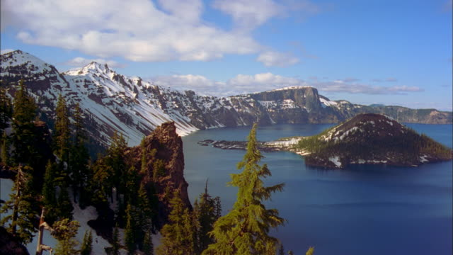 Clouds flow over Crater Lake and snowy mountains.