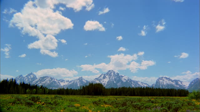 stockvideo's en b-roll-footage met clouds flow over the teton range mountains and a valley. - mount moran