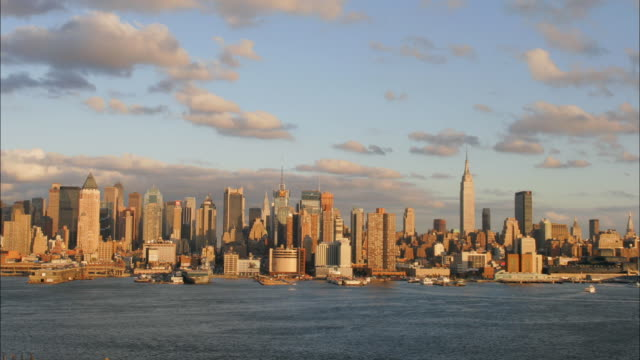 stockvideo's en b-roll-footage met clouds fly above the manhattan skyline as boats travel along the hudson river in new york city. - 2007