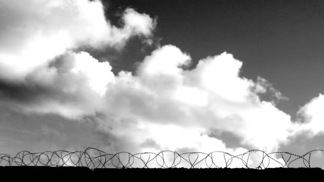 clouds fly over the fence with barbed wire (black and white) (time lapse) - government building stock videos & royalty-free footage